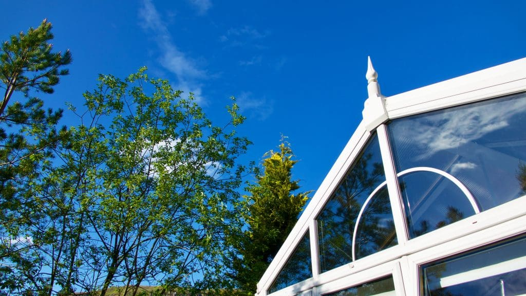 Close-up of a gable conservatory with trees in the background